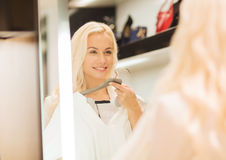 Mujer joven feliz que elige la ropa en alameda Imágenes de archivo libres de regalías