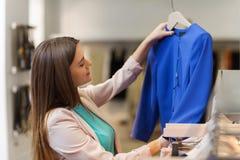 Mujer joven feliz que elige la ropa en alameda Fotos de archivo