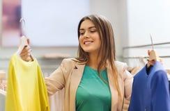 Mujer joven feliz que elige la ropa en alameda Foto de archivo libre de regalías
