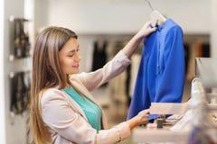 Mujer joven feliz que elige la ropa en alameda Fotos de archivo libres de regalías