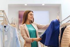 Mujer joven feliz que elige la ropa en alameda Imagenes de archivo