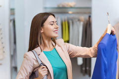 Mujer joven feliz que elige la ropa en alameda Fotografía de archivo libre de regalías