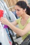 Mujer joven feliz que elige la ropa en tienda de ropa Foto de archivo