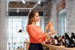 Mujer joven feliz que elige los zapatos en la tienda imagenes de archivo