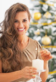 Mujer joven feliz que enciende la vela delante del árbol de navidad Imagen de archivo