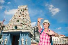 Mujer joven feliz que enmarca en el templo de Sri Mariamman, Singapur Imágenes de archivo libres de regalías
