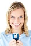 Mujer joven feliz que escribe un mensaje en su teléfono Foto de archivo libre de regalías