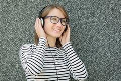 Mujer joven feliz que escucha la música con los auriculares Foto de archivo