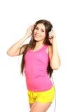 Mujer joven feliz que escucha la música en un fondo blanco Foto de archivo libre de regalías