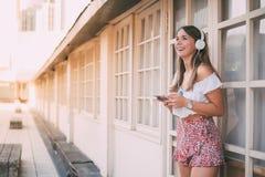 Mujer joven feliz que escucha la música en el teléfono móvil Foto de archivo libre de regalías