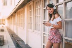 Mujer joven feliz que escucha la música en el teléfono móvil Fotografía de archivo