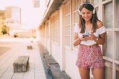 Mujer joven feliz que escucha la música en el teléfono móvil Fotografía de archivo libre de regalías