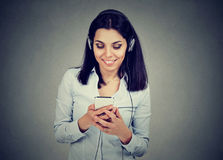 Mujer joven feliz que escucha la música en el teléfono móvil imagen de archivo libre de regalías