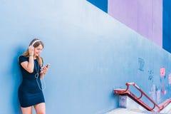 Mujer joven feliz que escucha la música en el teléfono móvil por un co Fotografía de archivo libre de regalías