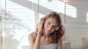 Mujer joven feliz que escucha la música en los auriculares y que baila mirando la cámara metrajes