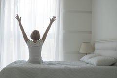 Mujer joven feliz que estira en cama después de despertar, visión trasera imagen de archivo