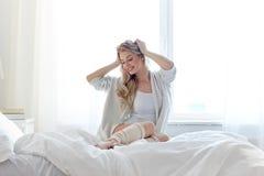 Mujer joven feliz que estira en cama en casa Imagenes de archivo