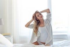 Mujer joven feliz que estira en cama en casa Foto de archivo libre de regalías