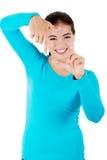 Mujer joven feliz que gesticula el marco Imágenes de archivo libres de regalías