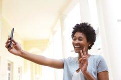 Mujer joven feliz que gesticula un signo de la paz y que toma el selfie Foto de archivo