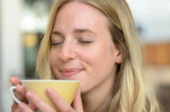 Mujer joven feliz que goza de su café de la mañana imágenes de archivo libres de regalías