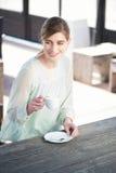 Mujer joven feliz que goza de una taza de café en un o Fotografía de archivo