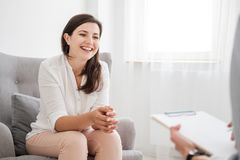 Mujer joven feliz que habla con un experto financiero sobre un préstamo para foto de archivo