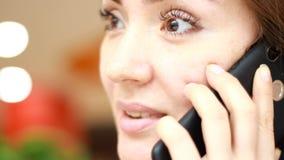 Mujer joven feliz que habla en el primer del teléfono celular almacen de metraje de vídeo