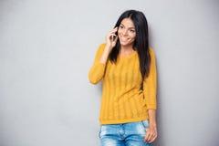 Mujer joven feliz que habla en el teléfono Imagenes de archivo