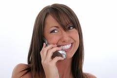 Mujer joven feliz que habla en el teléfono celular Imágenes de archivo libres de regalías