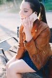 Mujer joven feliz que habla en el teléfono elegante del teléfono elegante en un parque de la ciudad que se sienta en un banco fotos de archivo
