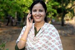Mujer joven feliz que habla en el teléfono móvil Imágenes de archivo libres de regalías