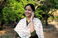 Mujer joven feliz que habla en el teléfono móvil Foto de archivo