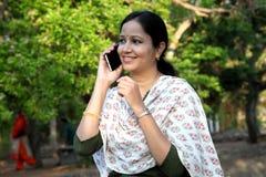 Mujer joven feliz que habla en el teléfono móvil Fotografía de archivo