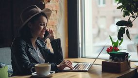 Mujer joven feliz que habla en el teléfono móvil y que usa el ordenador portátil que mecanografía en café metrajes