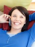 Mujer joven feliz que habla en el teléfono que miente en un sofá Fotos de archivo libres de regalías