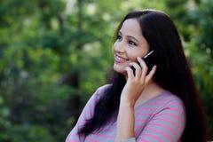 Mujer joven feliz que habla en móvil en al aire libre Imágenes de archivo libres de regalías