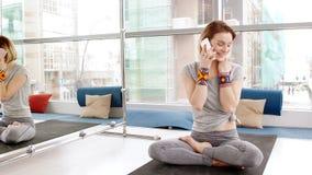 Mujer joven feliz que habla en smartphone en sitio de la yoga almacen de video