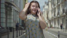 Mujer joven feliz que habla por el teléfono celular que camina a través de la calle de la ciudad Muchacha de la diversión que lle almacen de video