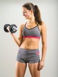 Mujer joven feliz que hace el rizo de la pesa de gimnasia Imagen de archivo