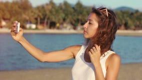Mujer joven feliz que hace el selfie en la playa de la playa almacen de video