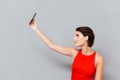 Mujer joven feliz que hace la foto del selfie en smartphone Fotos de archivo libres de regalías
