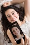 Mujer joven feliz que hace un selfie en cama Fotos de archivo