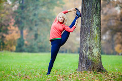 Mujer joven feliz que hace yoga en parque fotografía de archivo