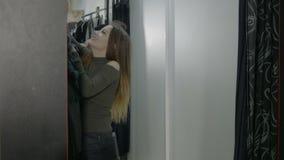 Mujer joven feliz que intenta en las diversas chaquetas de la marca en la alameda de compras y que decide cuál cabe mejor - metrajes