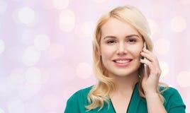 Mujer joven feliz que invita a smartphone Fotos de archivo