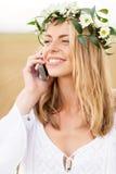 Mujer joven feliz que invita a smartphone en el país Fotografía de archivo libre de regalías