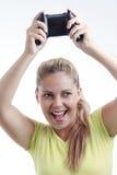 Mujer joven feliz que juega al videojuego con la palanca de mando Foto de archivo libre de regalías