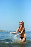 Mujer joven feliz que juega en la playa Fotografía de archivo