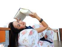 Mujer joven feliz que lee un libro en casa Imagen de archivo